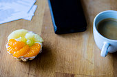 Tasty muffin with fruit on a wooden kitchen table. Coffee and phone with notes. Atmosphere.