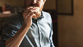 Hungry young hipster man eating a tasty sandwich with ham, hand close up