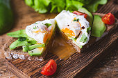 Poached egg, avocado snack toast sandwich on wooden cutting board. Close up view, selective focus