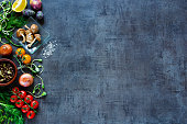 Raw organic vegetables with fresh ingredients for healthily cooking on vintage background, top view, banner. Vegan or diet food concept. Background layout with free text space.