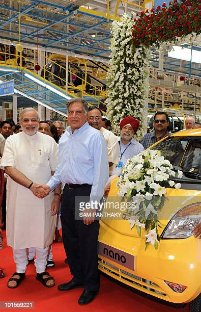 Tata Group chairman Ratan Tata and Gujarat state Chief Minister Narendra Modi pose besides a Nano car during a rollout ceremony at the new Nano plant...