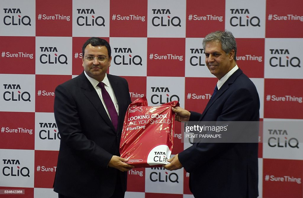 Tata Sons Chairman Cyrus Mistry (L) receives the first delivery packet from Chairman of Trent Ltd and Managing Director of Tata International Noel Tata during the launch of the 'Cliq' online store in Mumbai on May 27, 2016. India's Tata Group has launched a shopping website to target the country's growing online shoppers. / AFP / PUNIT