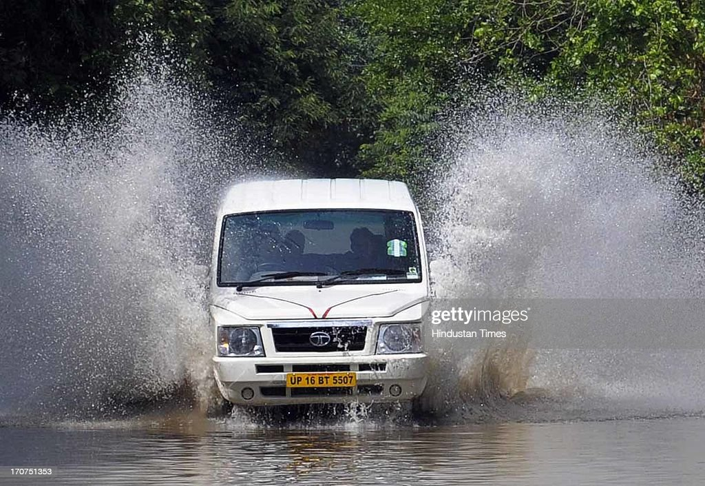 A Tata Sumo car move through in rain water logging at sector-31, on June 17, 2013 in Gurgaon, India. The city received 60 mm of rainfall.