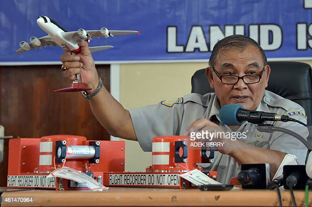 Tatang Kurniadi the head of the National Transportation Safety Committee speaks to journalists while using samples of the flight data recorder and...