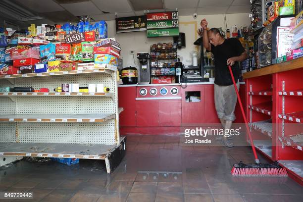 Tatang Sutardi sweeps the water out of the Blue Marlin store after it was damaged by hurricane Irma on September 19 2017 in Marathon Florida The...