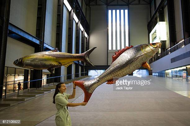 Tate employee pictured with inflatable floating fish during a photo call for a new installation by French artist Philippe Parreno titled 'Anywhen' at...
