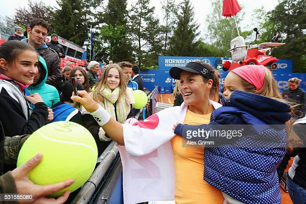 Tatjana Maria of Germany signs autographs with her daughter Charlotte after defeating Antonia lottner of Germany during Day Two of the Nuernberger...