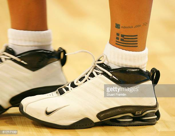 A tatoo of the Greek flag is seen on a Greek player below a tatoo of the AThens Olympics logo during the women's basketball quarterfinal game on...