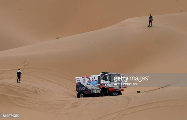 Tatra's Czech truck driver Martin Kolomy and codriver Jiri Stross and Michal Ernst halt among sand dunes as they compete during the Stage 12 of the...