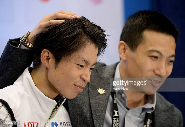 Tatsuki Machida of Japan reacts after his skate with coach Anthony Liu of Australia during the men's short program at Skate America 2013 at Joe Louis...