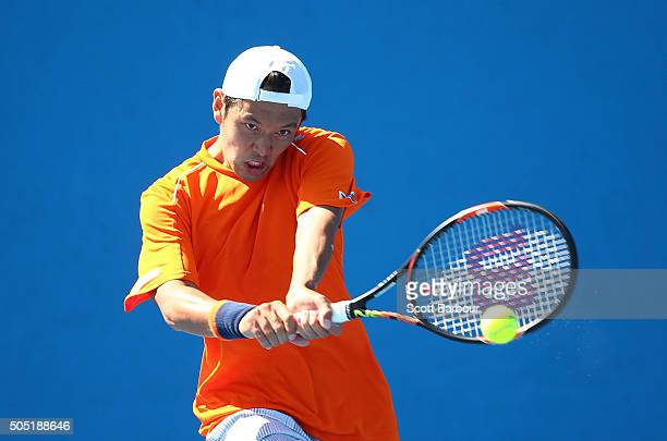 Tatsuma Ito of Japan plays a backhand in his match against Adrian MenendezMaceiras of Spain during the third round of 2016 Australian Open Qualifying...