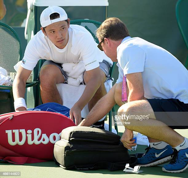 Tatsuma Ito of Japan receives attention from a trainer in his match against Malek Jaziri of Tunisia during the BNP Parisbas Open at the Indian Wells...