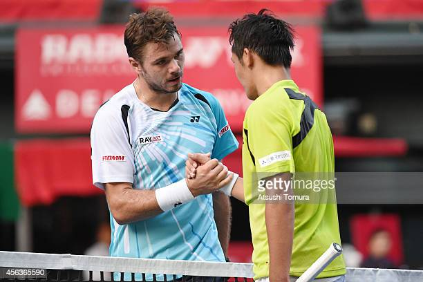 Tatsuma Ito of Japan shakes hands with Stan Wawrinka of Switzerland after winning their men's singles first round match on day two of Rakuten Open...