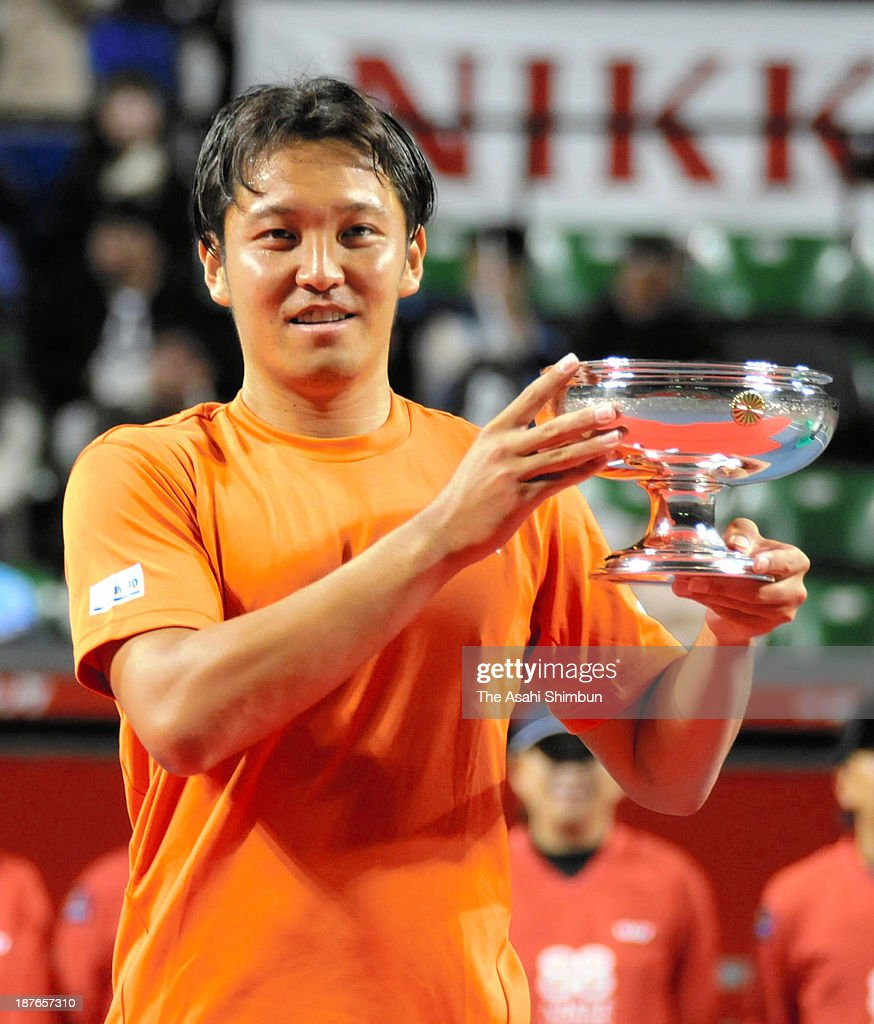 Tatsuma Ito poses for photographs with the trophy after winning in the Men's Singles on day eight of the 88th All Japan Tennis Championships at Ariake Colosseum on November 10, 2013 in Tokyo, Japan.