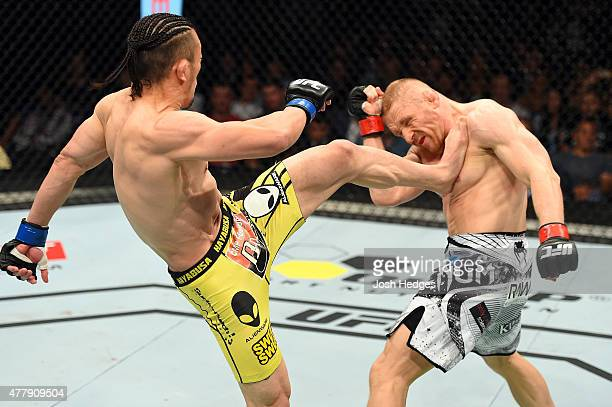 Tatsuya Kawajiri of Japan lands a kick to the chest of Dennis Siver of Germany in their featherweight bout during the UFC Fight Night event at the O2...