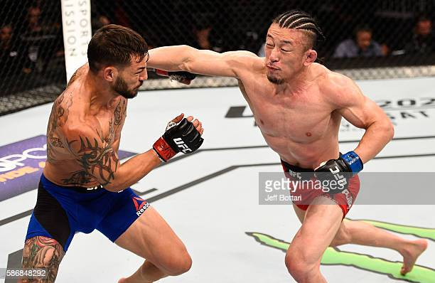 Tatsuya Kawajiri of Japan punches Cub Swanson in their featherweight bout during the UFC Fight Night event at Vivint Smart Home Arena on August 6...