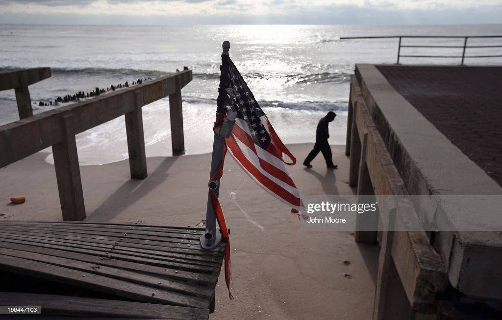 A tattered flag flies over the storm-damaged boardwalk on November 15, 2012 in the Rockaway neighborhood of the Queens borough of New York City. More than two weeks after Superstorm Sandy, emergency workers are still restoring power, water and heat to the battered community.