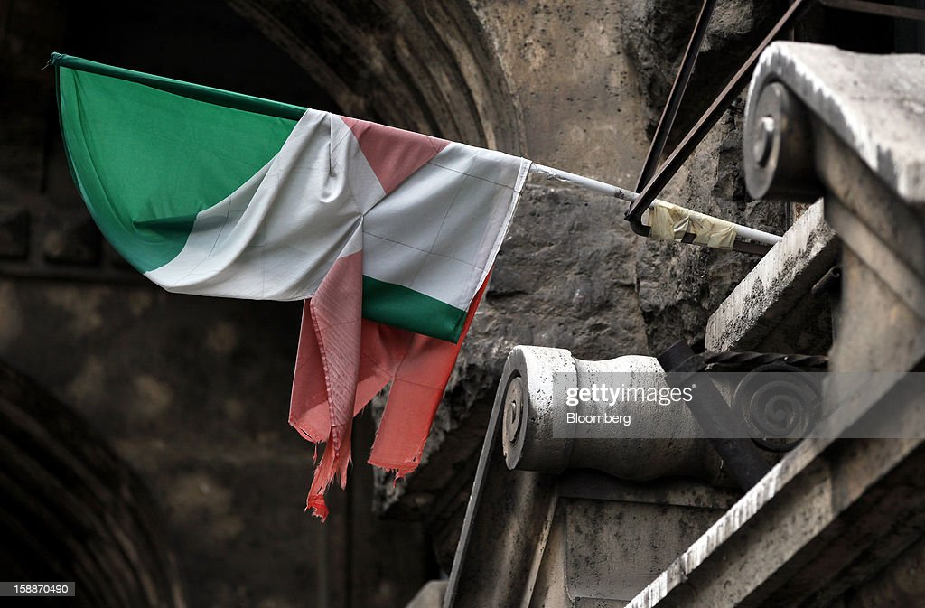 A tattered Italian national flag hangs from the facade of a residential apartment block in the Coppede district of Rome, Italy, on Wednesday, Jan. 2, 2013. Italian property sales often are reported to be less than the actual price paid to reduce taxes or skirt controls on money laundering, according to the website of the finance police, which reports to Italian Finance Minister Vittorio Grilli. Photographer: Alessia Pierdomenico/Bloomberg via Getty Images