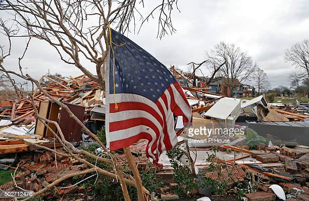 A tattered US flag that had been attatched to a tree waves over the debris at the Landmark at Lake Village North Apartments as the recovery process...