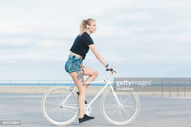 Tattoed Girl Passing By on White Fixie at Blue Seaside