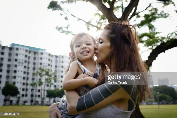 Tattoed mom holding her toddler son in a park