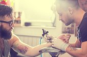 Male tattoo artist holding a tattoo gun, showing a process of making tattoos on a male tattooed model's arm.
