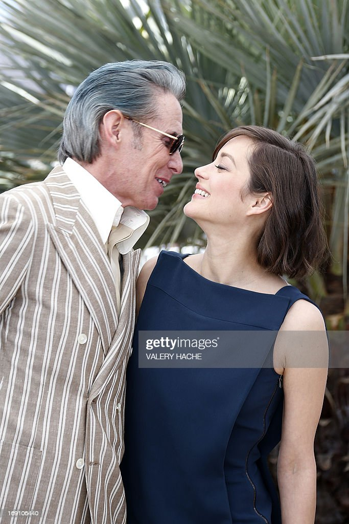 US tattoo artist and actor Mark Mahoney (L) and French actress Marion Cotillard pose on May 20, 2013 during a photocall for the film 'Blood Ties' presented Out of Competition at the 66th edition of the Cannes Film Festival in Cannes. Cannes, one of the world's top film festivals, opened on May 15 and will climax on May 26 with awards selected by a jury headed this year by Hollywood legend Steven Spielberg. AFP PHOTO / VALERY HACHE