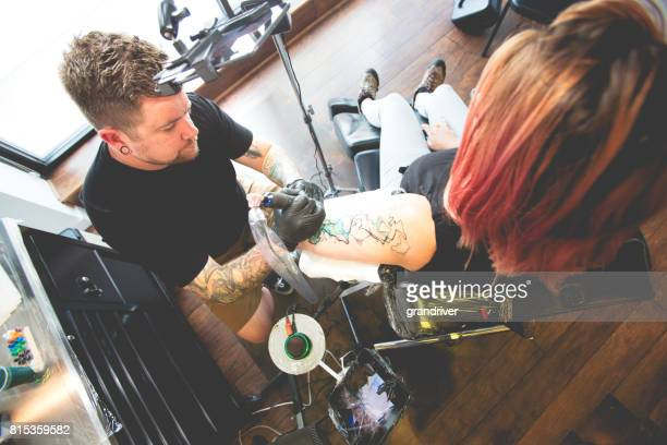 Tattoo Artist Creating New Tattoo on a Young Woman