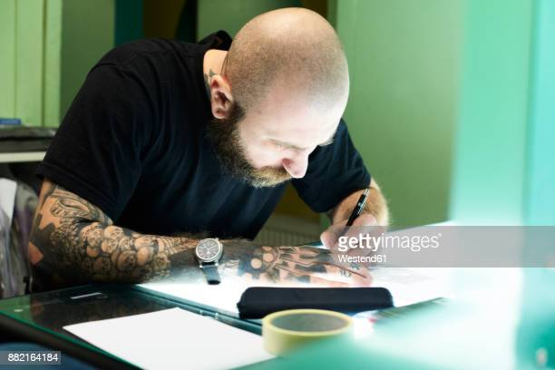 Tattoo artist designing motif on light table in studio