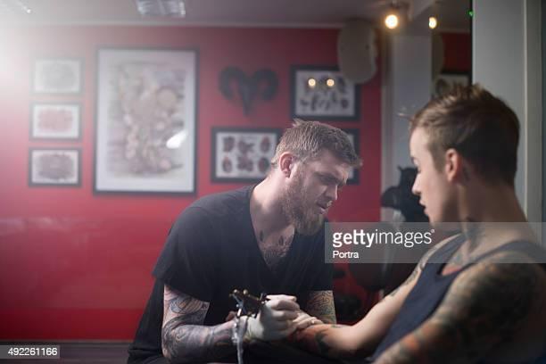 Tattoo artist untersuchen Kunden hand in studio