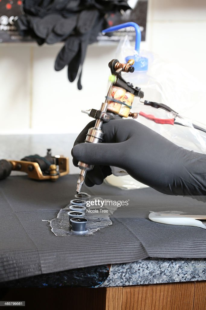 Tattoo artist getting ink into tattoo gun : Stock Photo