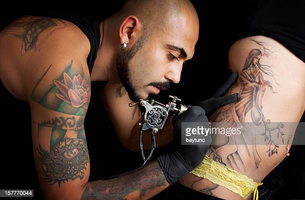 A tattoo artist giving a customer a tattoo