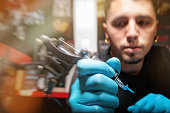 Tattoo artist holding tattoo gun with needle attached