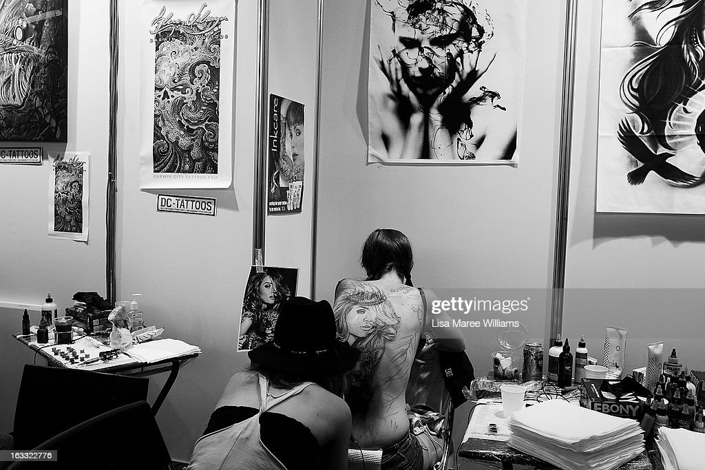 Tattoo artist Kristen Sorrenson of 'Garage Ink' works on a young woman's back during The Australian Tattoo & Body Art Expo at the Royal Hall of Industries, Moore Park on March 8, 2013 in Sydney, Australia. The annual three day event showcases some of Australia's best tattoo and body artists and is open to enthusiasts March 8-10.