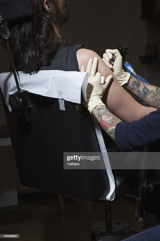A tattoo artist preparing to tattoo a man's bare arm : Stock Photo