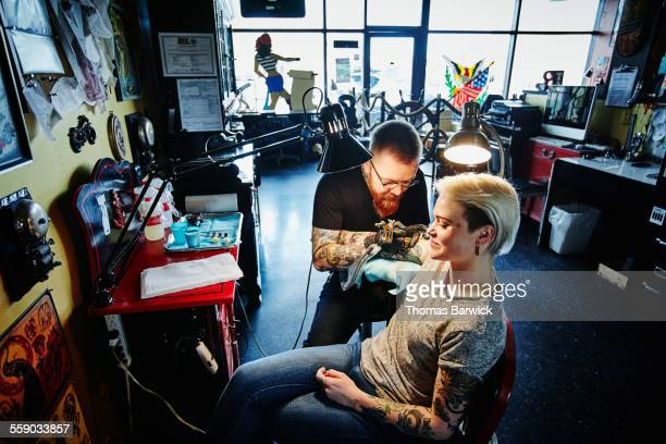 Tattoo artist tattooing arm of female customer
