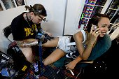 A tattoo artist works on a woman's leg during the 'Expo Tatoo Venezuela' in Caracas on January 29 2015 AFP PHOTO/FEDERICO PARRA