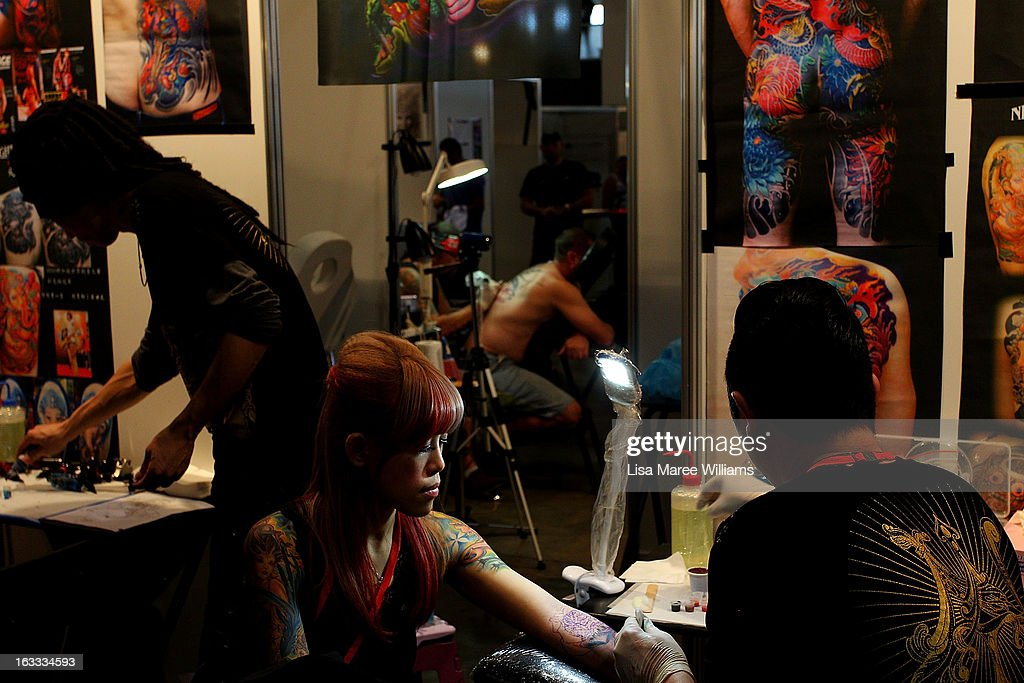Tattoo artists from 'Night Action Tattoo' in Taiwan work on clients during The Australian Tattoo & Body Art Expo at the Royal Hall of Industries, Moore Park on March 8, 2013 in Sydney, Australia. The annual three day event showcases some of Australia's best tattoo and body artists and is open to enthusiasts March 8-10.