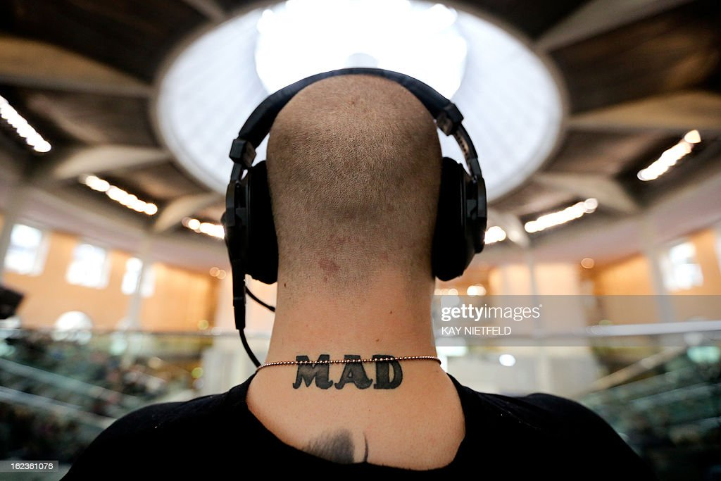 A tattoo is seen on a neck of a cameraman following a session of the German parliament at the Reichstag building in Berlin, Germany, on February 22, 2013.