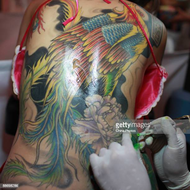 A tattoo maker gives tattoo to a man during the Changchun Tattoo Art Festival on June 26 2009 in Changchun of Jilin Province China Numbers of...