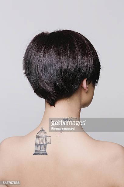 Tattoo of bird outside cage on woman's shoulder