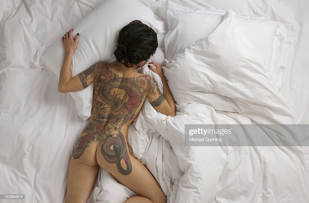 Tattoo woman on sheets : Stock Photo