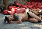 A tattooed activist of the People for the Ethical Treatment of Animals and Anima Naturalis proanimal groups sporting horns lies on the ground during...