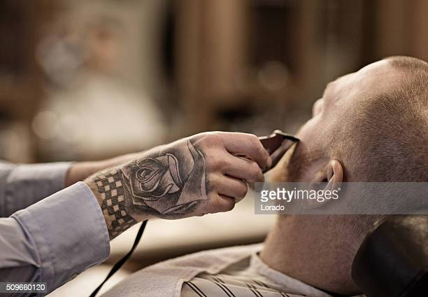 Tatuado Barbeiro com cliente barbudo homem Careca