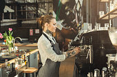 Young tattooed barista making coffee in professional coffee machine. Woman preparing beverage. Small business and professional coffee brewing concept
