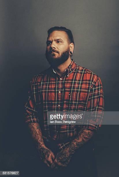 Tattooed, bearded man in plaid shirt