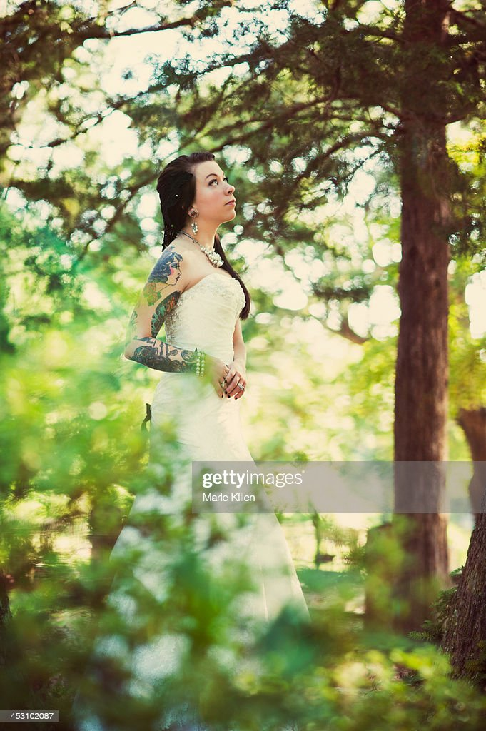 Tattooed Bride looking up surrounded by trees : Stock Photo