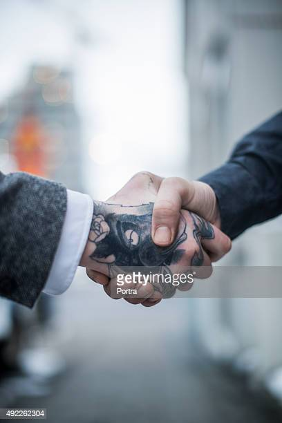 Tattooed businessman shaking hand with colleague