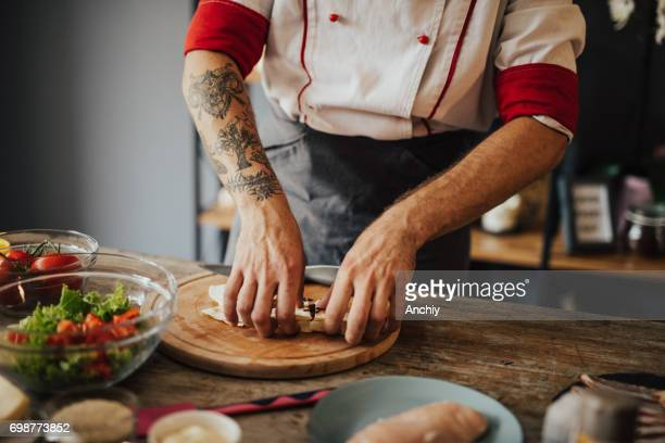 Tattooed chef prepares meal at home