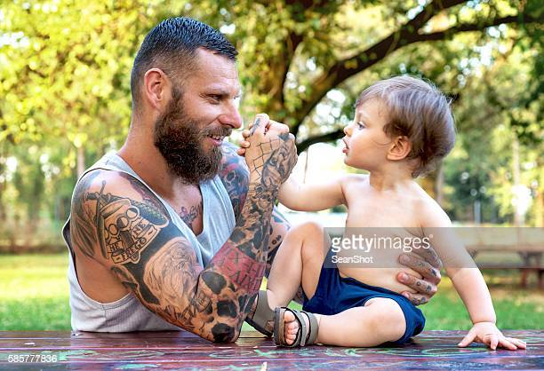 Tattooed Father and Son Playing in the Park